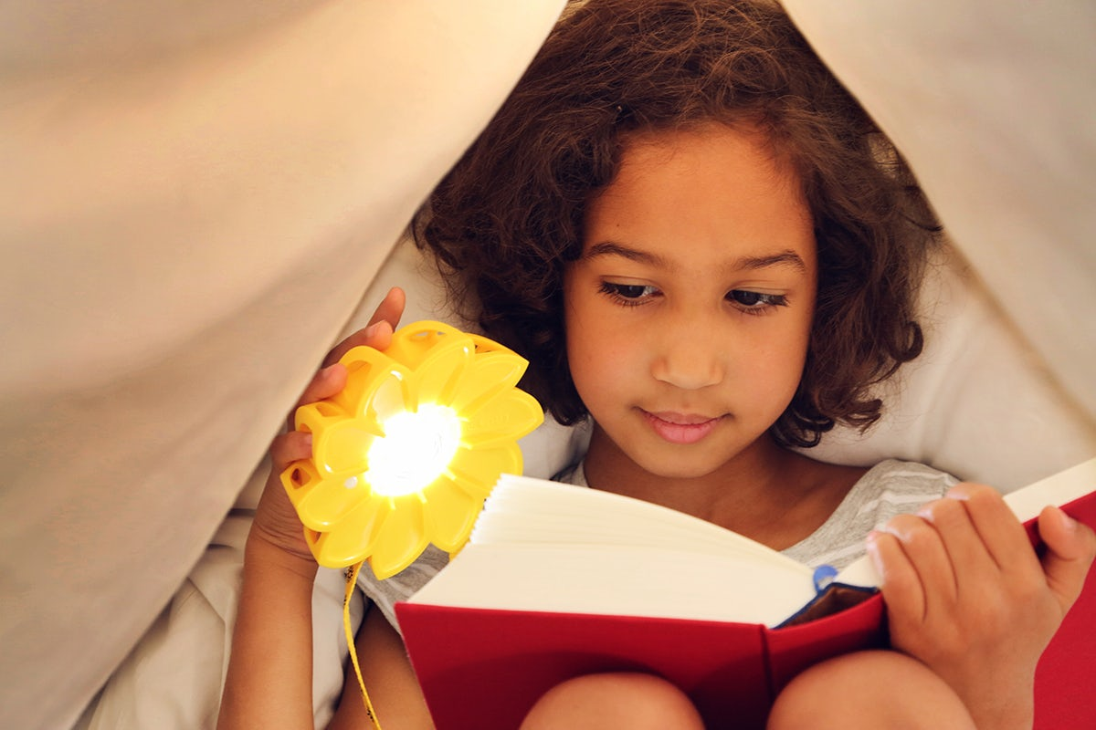 Reading with the original Little Sun light. Image: Franziska Russo