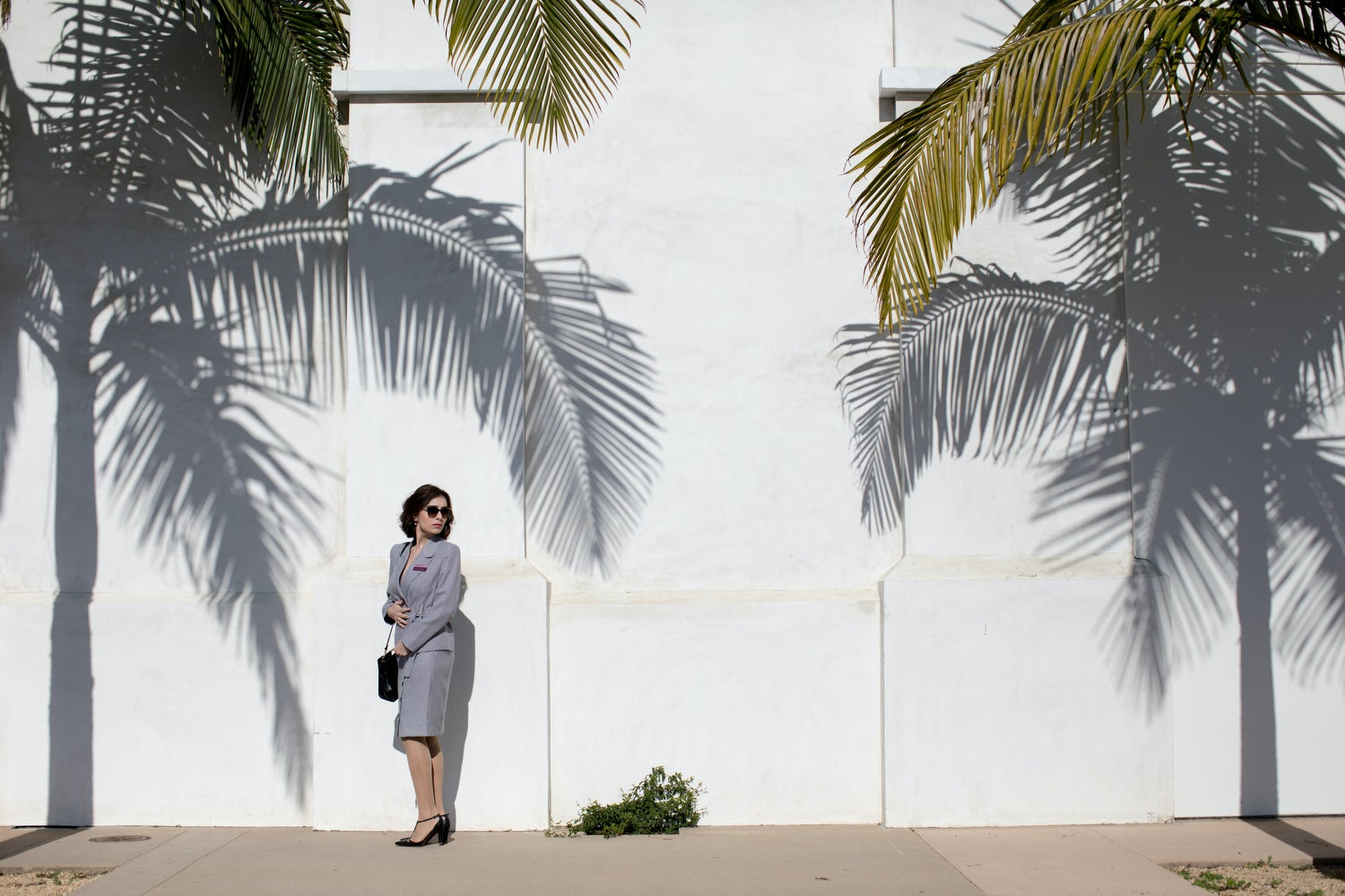 Actor playing Diana Markosian mother stood by a wall under palm trees
