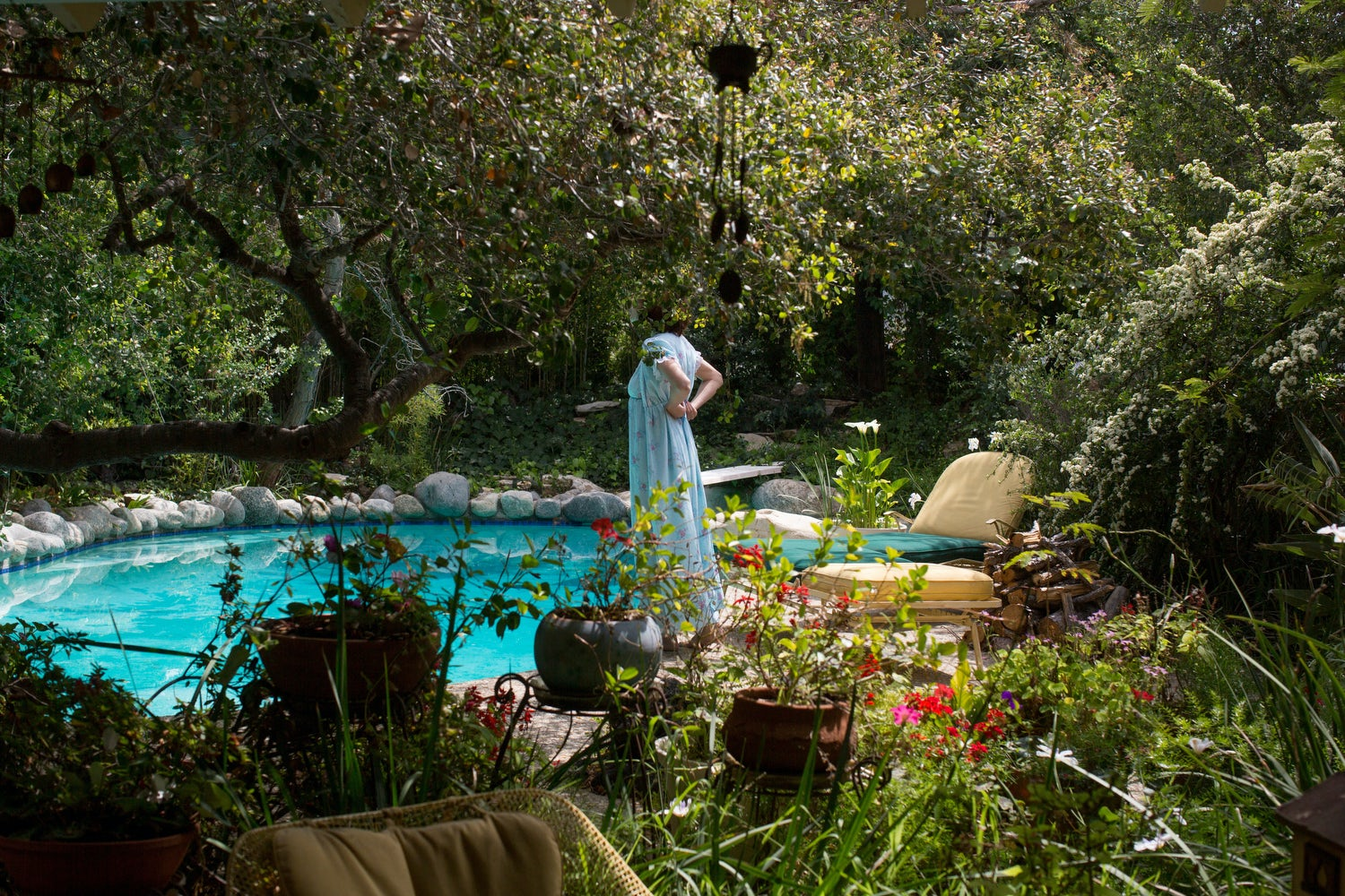 Actor playing the mother of Diana Markosian stood by a pool, her head concealed by a tree